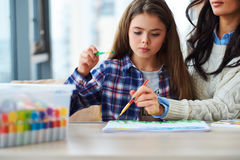 Pretty little girl with her mother painting picture at home Stock Images