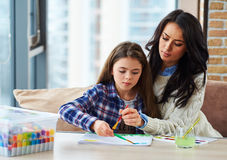 Pretty little girl with her mother painting picture at home Stock Photos