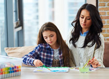 Pretty little girl with her mother painting picture at home Stock Photo