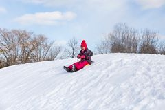 Pretty little girl in her ski suit screaming of joy while sliding down a small snow. Pretty little girl in her ski suit screaming of joy while starting to slide Royalty Free Stock Photography