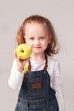 Pretty little girl holding apple in studio Stock Photos
