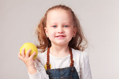 Pretty little girl holding apple in studio Royalty Free Stock Photos