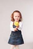 Pretty little girl holding apple in studio Stock Photo