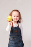 Pretty little girl holding apple in studio Royalty Free Stock Image