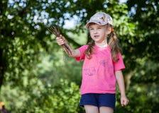 Pretty little girl holding brushwood Royalty Free Stock Photos