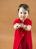 Pretty little girl holding donuts at brown background Stock Photo