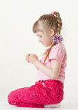 Pretty little girl holding and examining something Royalty Free Stock Photo