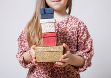 Pretty little girl holding gift boxes Royalty Free Stock Image