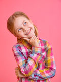 Pretty little girl holding hand chin and looking up Stock Images