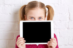 Pretty little girl holding and hiding behind the laptop. Copy space. Royalty Free Stock Photography