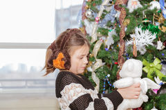 Pretty little girl  holding and looking at plush angel bear toy beside Christmas tree Stock Photos