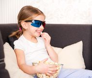 Little girl watching TV. Pretty little girl holding popcorn and watching 3d TV Royalty Free Stock Photography