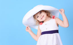 Pretty little girl holding summer hat on blue Stock Images