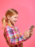 Pretty little girl holding a tablet on pink background in profile. Stock Photos