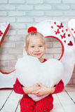 Pretty little girl holding toy heart Royalty Free Stock Photo