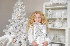 Pretty little girl holds a gift box at hands and smiles in a light new year decoration studio Stock Images
