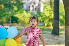 Pretty little girl holds in hands balloons Stock Photos