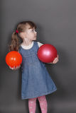 Pretty little girl in jeans dress holds two balls Stock Image