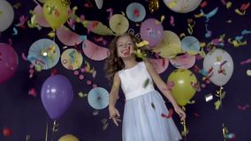Pretty little girl jumping under bright confetti and celebrating birthday party. Pretty little girl jumping under bright confetti and celebrating her birthday stock video