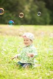 Pretty little girl is laughing and playing with soap bubbles Royalty Free Stock Image