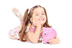 Pretty little girl laying on floor with piggybank stock images