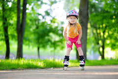Pretty little girl learning to roller skate  outdoors Stock Images
