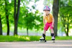 Pretty little girl learning to roller skate  outdoors Stock Image