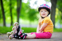 Pretty little girl learning to roller skate  outdoors Royalty Free Stock Photography