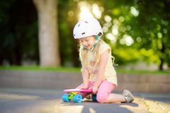 Pretty little girl learning to skateboard on beautiful summer day in a park. Child enjoying skateboarding ride outdoors. Stock Photography