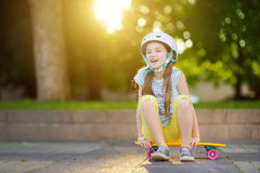 Pretty little girl learning to skateboard on beautiful summer day in a park. Child enjoying skateboarding ride outdoors. Royalty Free Stock Images