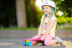 Pretty little girl learning to skateboard on beautiful summer day in a park. Child enjoying skateboarding ride outdoors. Stock Images