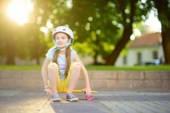 Pretty little girl learning to skateboard on beautiful summer day in a park. Child enjoying skateboarding ride outdoors. Stock Photos