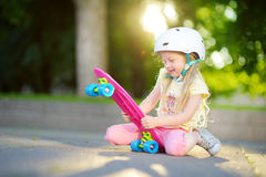 Pretty little girl learning to skateboard on beautiful summer day in a park. Child enjoying skateboarding ride outdoors. Stock Image