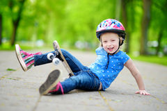 Pretty little girl learning to skateboard outdoors Stock Photo