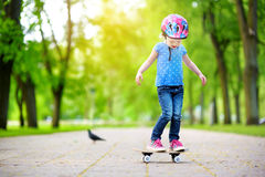 Pretty little girl learning to skateboard outdoors Royalty Free Stock Photo