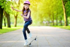 Pretty little girl learning to skateboard outdoors Stock Photos