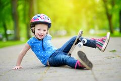 Pretty little girl learning to skateboard outdoors Royalty Free Stock Photography