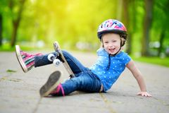 Pretty little girl learning to skateboard outdoors Royalty Free Stock Photos
