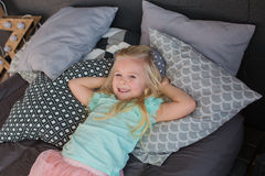 A pretty little girl lies on a bed and smiles. A little girl lies on a bed and smiles Stock Image