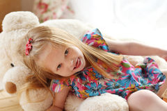 Pretty little girl lies on big soft toy bear Stock Photos