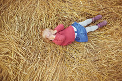 A pretty little girl lies on a ears of wheat and closes his eyes Royalty Free Stock Image