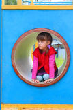 Pretty little girl lies in pipe on playground Royalty Free Stock Image