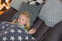 Pretty little girl lies under a plaid and smiles. A pretty little girl lies under a plaid in a bed and smiles Royalty Free Stock Photography