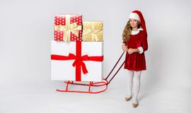 Stunning beautiful little girl with long blond, dressed in a red cap Santa Claus and elegant clothes. Pretty little girl with long blond hair standing on a white Royalty Free Stock Images