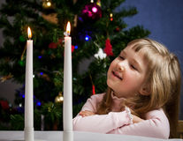 Pretty little girl looking on fire of candles Royalty Free Stock Photos