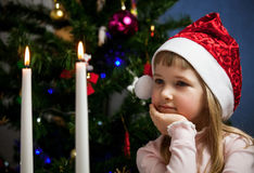 Pretty little girl looking on fire of candles Stock Image