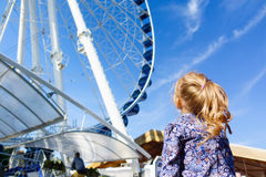 Pretty little girl looks at ferris wheel against a blue sky Stock Image