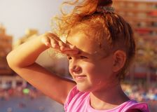 A pretty little girl looks to far away from right to left side, smiling and squinting in sunshine on city beach background. Sunset Stock Photo