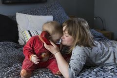 Pretty little girl lying on bed holding vintage red phone receiver to her baby sister`s ear stock image