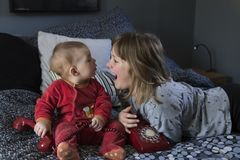 Pretty little girl lying on bed laughing out loud and her cute chubby baby sister in pyjamas sitting on bed stock photography